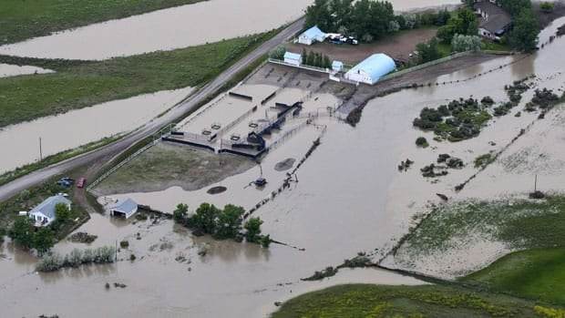A prairie farm sits flooded along the Trans-Canada highway.