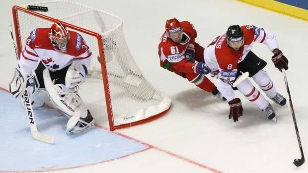 Canadian goaltender James Reimer, left, looks on as teammate Brent Burns, right, controls the puck ahead of Belarus's Andrei Stepanov Friday at the world championships in Kosice, Slovakia.