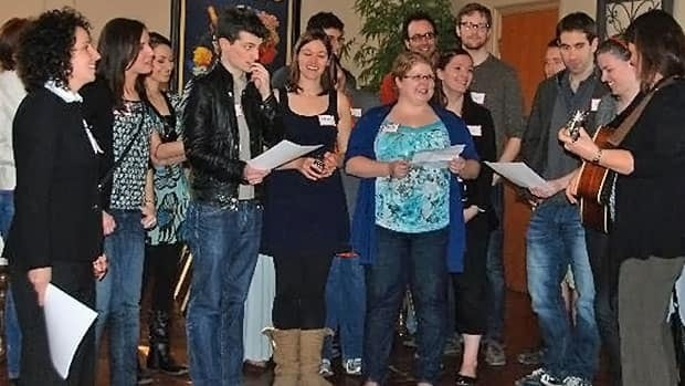 Students from the Graduate Program in Journalism at Western, sing at a reception for A Good Death, April 2011. Professor Meredith Levine is on the far left.