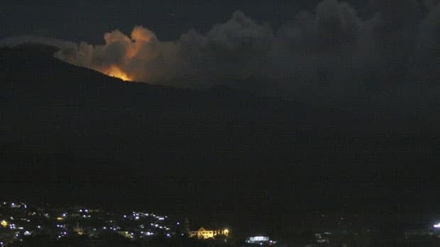 The glow of lava from Mount Lokon's eruption is seen against the night sky in Manado, North Sulawesi, Indonesia, early Friday. The volcano spit lava and smoke, sending panicked residents fleeing down its slopes.