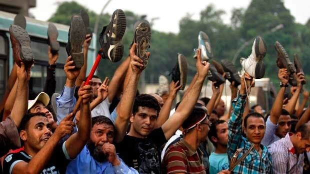 Egyptians near the Israeli embassy in Cairo hold their shoes up to protest the deaths of Egyptian security forces killed in a shootout between Israeli soldiers and Palestinian militants.
