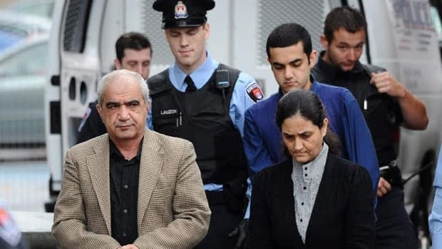 Mohammad Shafia, his wife Tooba, Mohammad Yahya, and their son, Hamed Mohammed Shafia, are escorted by police officers into the Frontenac County Court House on the first day of their trial in Kingston, Ont., in October.