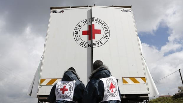 Workers from the Red Cross stand near the Israel-Syria border earlier this year. Syria's state news agency, quoting an anonymous official, said gunmen opened fire on a Red Cross team's four vehicles before seizing the Red Cross workers.