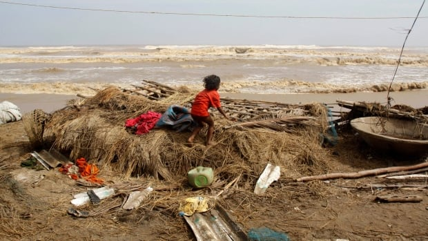 An Indian child searches for belongings on Sunday amid the remains of her damaged house on the Bay of Bengal coast after returning to the cyclone-hit village of Podampeta in Ganjam district, Orissa state, A mass evacuation before Cyclone Phailin roared ashore kept the death toll down.