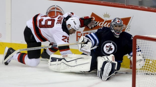 New Jersey Devils' Ryane Clowe (29) gets tangled up with Winnipeg Jets goaltender Al Montoya (35) during third period NHL hockey action in Winnipeg, Sunday, October 13, 2013. THE CANADIAN PRESS/Trevor Hagan