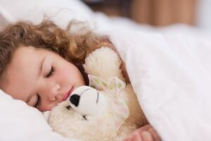 Girl sleeping with her teddy