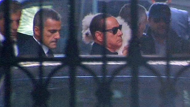 Flanked by bodyguards and carrying his pet dog, Silvio Berlusconi is shown here entering one of his palatial Rome residences in September, just hours after threatening to bring down the Letta coalition government. A week later, however, enough of his own party rebelled to keep the coalition functioning.