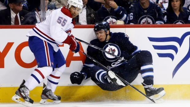 The Montreal Canadiens' Francis Bouillon trips up the Winnipeg Jets' Blake Wheeler during the second period Tuesday at the MTS Centre.