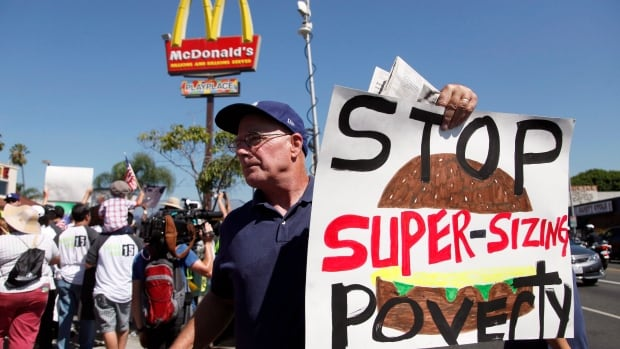Kevin Cole protests outside a fast food restaurant on Aug. 29 as fast-food workers walked out to demand higher wages.