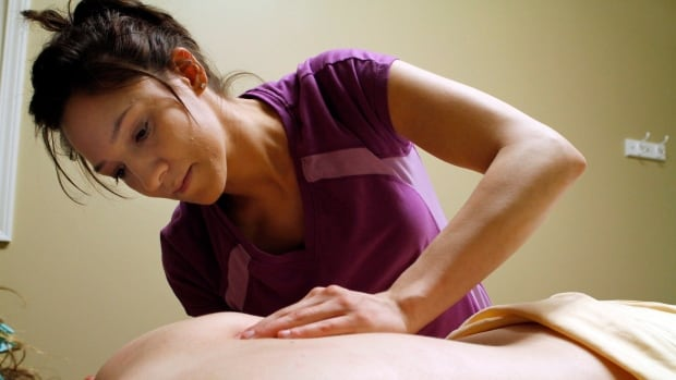 Esther Miller massages a client at her business, Anointed Massage. Massages are typically claimed by 27 per cent of Great-West Life's plan members. (AP Photo/Hutchinson News, Colleen Lefholz)