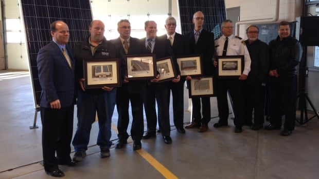 A group of city officials gather to celebrate the completion of six buildings with solar panels.
