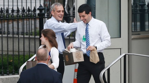 White House Chief of Staff Denis McDonough, centre, greets federal employees at the entrance to the Eisenhower Executive Office Building as he they return to the White House in Washington on Thursday.