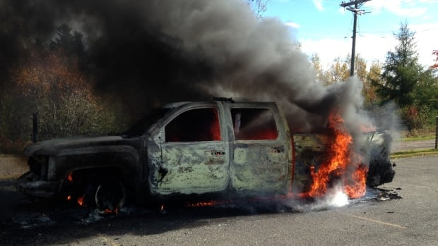 Cars burn at the scene of the Rexton shale gas protest that turned violent.