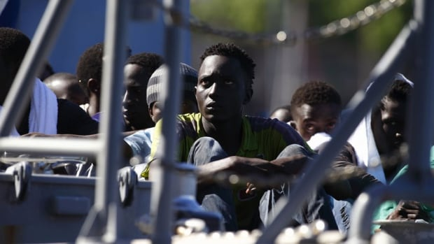 Rescued migrants sit on the deck of an Armed Forces of Malta (AFM) patrol boat at the AFM Maritime Squadron base at Haywharf in Valletta's Marsamxett Harbour. A U.S. Navy ship rescued 128 men from a raft after it was spotted in the Mediterranean Sea by a Maltese patrol aircraft.