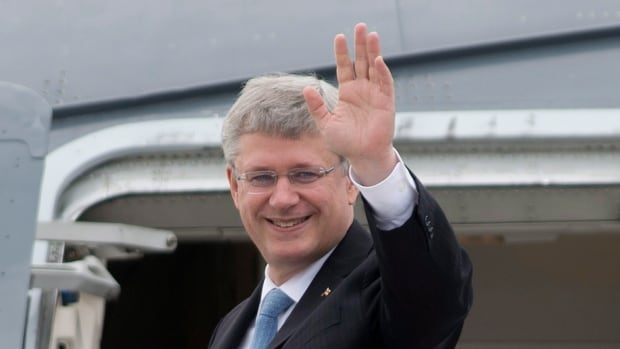 Prime Minister Stephen Harper waves as he departs for Europe from Ottawa on Thursday before the unveiling of a free trade treaty.