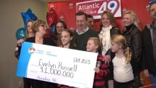 Evelyn Russell and her family holding cheque