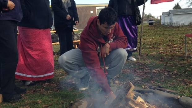 Chance King adds wood to a sacred fire in Thunder Bay at a ceremony to support anti-fracking protesters in New Brunswick.