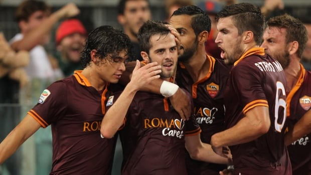 Roma's Miralem Pjanic, centre, celebrates with teammates after scoring the opening goal during against Napoli at Stadio Olimpico on October 18, 2013 in Rome, Italy.