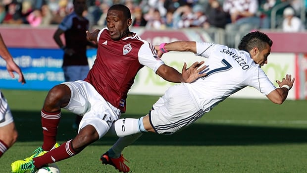 Vancouver Whitecaps forward Camilo Sanvezzo, right, is sent flying after getting tied up with Colorado Rapids midfielder Hendry Thomas.