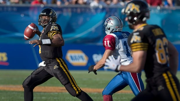 Hamilton Tiger-Cats quarterback Henry Burris, left, is chased by Montreal Alouettes Chip Cox in first half CFL action in Moncton, N.B. on Saturday, Sept. 21, 2013.