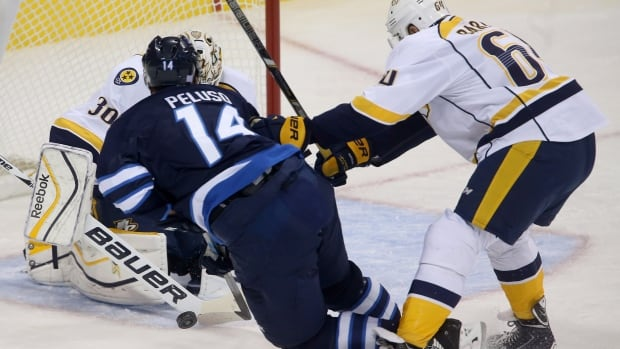 Winnipeg Jets' Anthony Peluso is tripped by Nashville Predators' Victor Bartley in front of goaltender Carter Hutton during first period of their game in Winnipeg on Sunday.