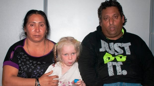 Selini Sali, 40, also known as Eleftheria Dimolpoulou, left, and Christos Salis, 39, right, are seen in a Greek police photo with the blond blue-eyed girl found in their care. They have been jailed pending trial, and are also suspected of fraudulently obtaining birth certificates for a total 14 children.
