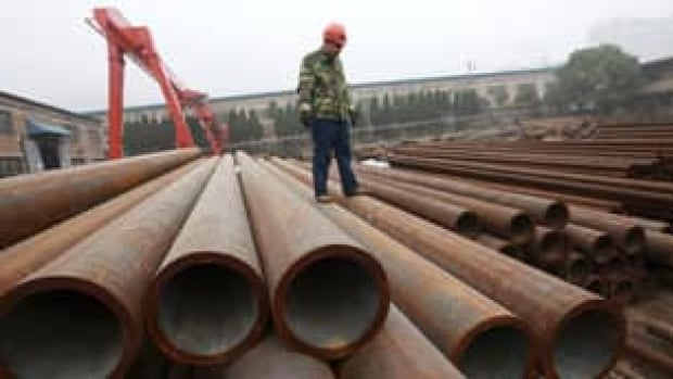 A worker stands on oilwell pipes at a factory in Huaibei, in central China's Anhui province. China criticized a U.S. decision to impose antidumping duties on Chinese-made pipes.