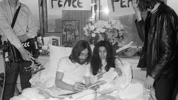 John Lennon (centre left) and Yoko Ono are flanked by journalists in Room 1742 of the Queen Elizabeth Hotel in Montreal. They settled into the corner suite rooms 1738,1740 and 1742 at midnight on May 26, 1969, and over the following seven days spoke and sang about peace with visiting guests.