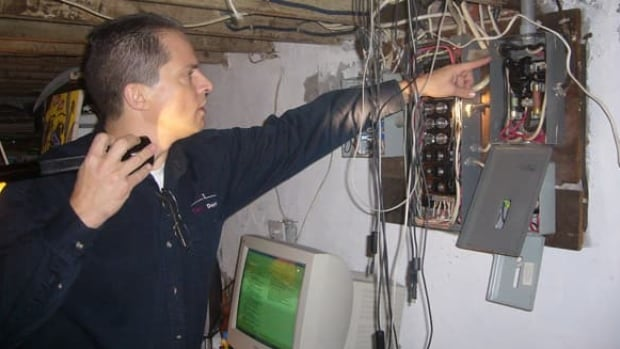 Tom Woolley checks to make sure the wires that run to the service panel are the right size for the circuit breakers or fuses in use.