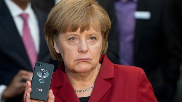 German Chancellor Angela Merkel shows a tap-proof BlackBerry mobile phone at a  trade show. The newsmagazine Der Spiegel has said the U.S. NSA may have monitored the chancellor's calls for more than 10 years.