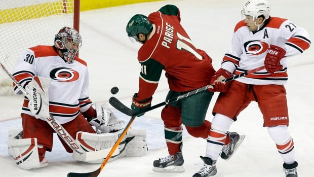 Hurricanes goalie Cam Ward blocks a shot off the stick of the Wild's Zach Parise, centre, on Thursday.