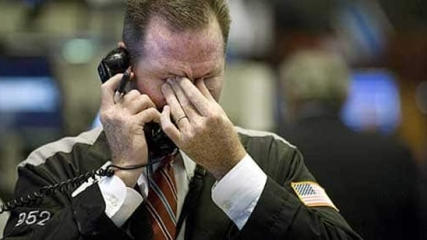 A trader watches the market board on a down day for stocks. After four days of gains, oil resumed its slide on Wednesday.