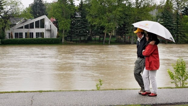 A couple walk along the swollen banks of the Elbow River in Calgary during last year's flood.