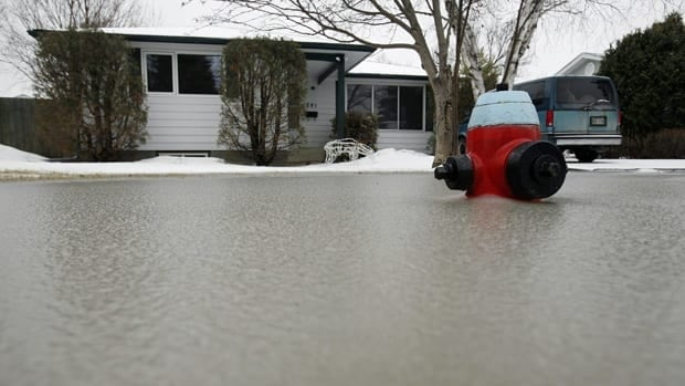 A home is threatened by flooding from melt water in south Winnipeg in March 2009. Officials recommend homeowners seal basement windows and ground-level doors and install a zero reverse flow valve in basement drains to limit any potential flood damage.
