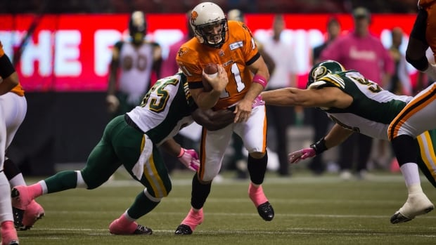 B.C. Lions' quarterback Buck Pierce, centre, gets away from Edmonton Eskimos' Rennie Curran, left, and Justin Capicciotti, right, and completes a pass to Andrew Harris for a touchdown on Friday.