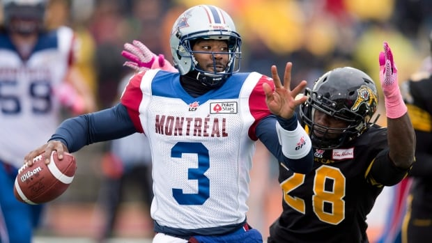 Montreal quarterback Troy Smith (3) makes a pass under heavy pressure from Hamilton Tiger-Cats linebacker Jamall Johnson (28) during first half CFL action in Guelph on Saturday October 26, 2013.
