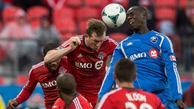 Toronto FC 's Steven Caldwell, left, clears the ball under pressure from Montreal Impact's Hassoun Camara during the second half in Toronto on Saturday.