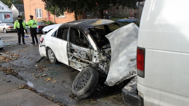 Police hold the scene of a car crash on Sunday morning that resulted in a vehicle catching fire and sent two to hospital.