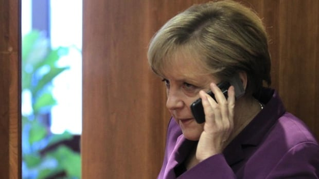 German Chancellor Angela Merkel uses her mobile phone before a 2011 meeting at a European Union summit in Brussels. News magazine Der Spiegel reported that an apparent NSA document indicates Merkel's phone was first listed as a target in 2002.