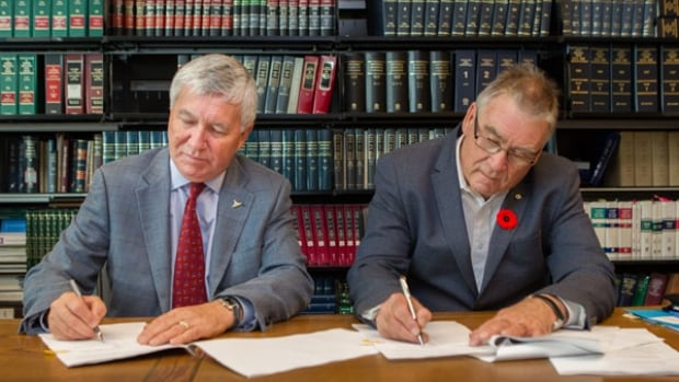 Mayor of Kitchener Carl Zehr and president of Andrin Homes Peter Smith finalize the purchase of the Centre Block land.