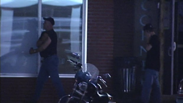 Members of the Outlaws Motorcycle Club hang around outside their clubhouse, next door to a local bar. Some residents and business owners have expressed concern about the club.