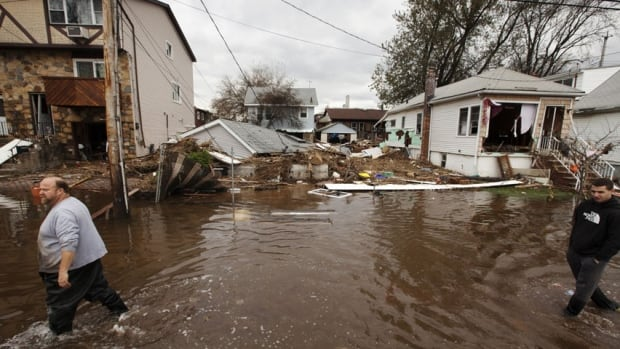 Men walk through the flooding left by the storm surge of superstorm Sandy in the New Dorp Beach neighbourhood of the Staten Island borough of New York on November 1, 2012. Property damage caused by the storm was estimated at $65 billion.