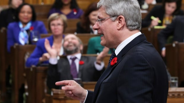 NDP Leader Tom Mulcair reacts as Prime Minister Stephen Harper answers a question on the Senate scandal in the House of Commons on Oct. 29.