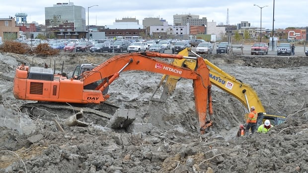 A second excavator moves in to help free up another machine that's sinking into wet clay at a demolition site in downtown Sudbury.
