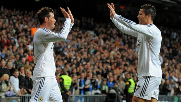 Gareth Bale of Real Madrid, left, celebrates with Cristiano Ronaldo against Sevilla at the Santiago Bernabeu Stadium on October 30, 2013 in Madrid, Spain.