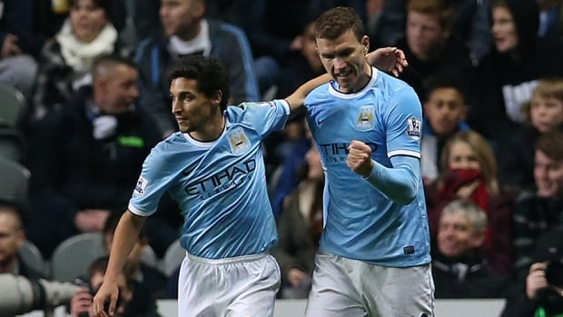 Manchester City striker Edin Dzeko, right, celebrates scoring against Newcastle United on October 30, 2013.