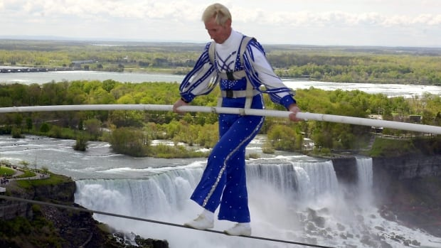Canadian daredevil Jay Cochrane, shown in 2002 completing his tight-rope walk in Niagara Falls, Ont., has died of cancer at age 69, according to his publicist.