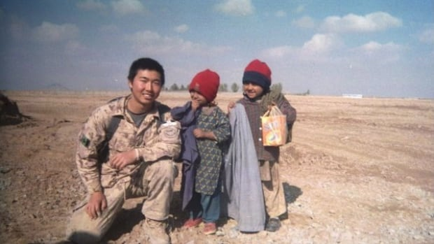 Canadian Cpl. David Hawkins poses with children in Afghanistan in a 2008 handout photo. Gravely injured troops who want to remain uniform are being booted from the military before they qualify for their pensions, despite assurances to the contrary from the Harper government.