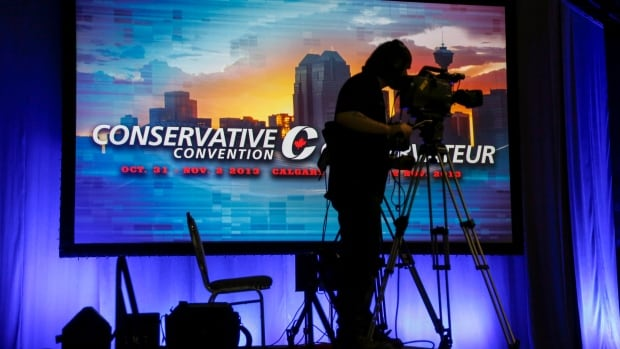 A cameraman adjusts his camera in the main hall at the Conservative convention in Calgary Thursday. Party members and MPs are gathering for the convention, which includes a keynote address by Prime Minister Stephen Harper on Friday.