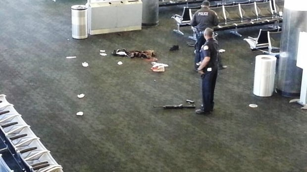 Police officers stand near an unidentified weapon in Terminal 3 of the Los Angeles International Airport on Friday after a gunman who opened fire in the terminal was wounded in a shootout with police and taken into custody.